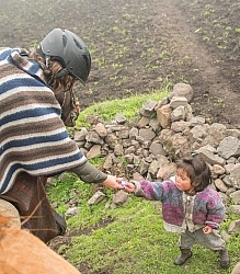 Ali gives a my little pony to a small Ecuadorian girl in the hig